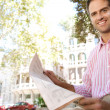 Senior businessman reading a newspaper while sitting down in a classic city square, outdoors. — Stock Photo