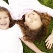 Overhead portrait of two girls laying down on green grass, laughing. — Stock Photo