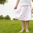 Close up detail of a young girl holding a soft toy in the park, body section. — Stock Photo #20204811