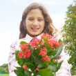 Young girl feeling proud, holding a plan pot with flowers in the park. - Stockfoto