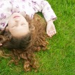 Over head view of a young girl laying down on green grass with her eyes shut. — Stock Photo