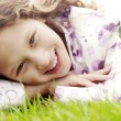 Portrait of a young girl laying down on green grass in the park — Stock Photo