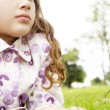 Stock Photo: Portrait of a young girl laying down on green grass in the park, looking ahead.
