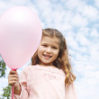 Portrait of a young smiling girl holding a pink balloon in the park on a sunny day. — Stock Photo #20204969