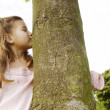 Young girl kissing a tree trunk in the park. — Stock Photo #20204999