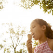 Portrait of a young girl eating an ice cream in the park, under golden light and trees. — Stock Photo