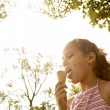 Portrait of a young girl eating an ice cream in the park, under golden light and trees. — Stock Photo #20205039