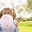 Young girl blowing a pink balloon in the park on a sunny day. — Stock Photo