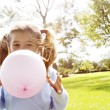 Young girl blowing a pink balloon in the park on a sunny day. — Photo