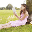 Young girl sitting on green grass in the park and reading a book while leaning on a tree trunk. — Stock Photo