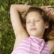 Stock Photo: Overhead close up portrait of a yougn girl laying down on green grass in the park.