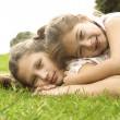 Two sisters laying down on top of each other and smiling in the park. — Стоковая фотография