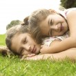 Two sisters laying down on top of each other and smiling in the park. — Foto de Stock