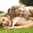 Two sisters laughing and playing in the park — Stock Photo