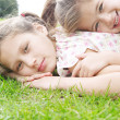 Two young sisters laying down on green grass in the park — Stock Photo #20205285