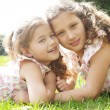 Stock Photo: Two sisters laying down on green grass in the park