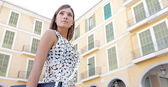 Young businesswoman walking passed classic office buildings in a city square. — Stock Photo