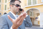 Portrait of an unhappy businessman having a discussion on his smart hpone while visiting a classic city. — Stock Photo
