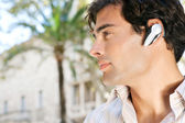 Young attractive businessman using a hands free device to have a conversation on his cell phone — Stock Photo