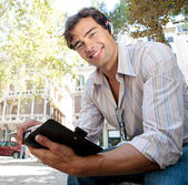 Young casual businessman using a hands free ear device to have a conversation — Stock Photo