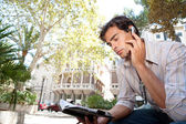 Side view of a young businessman using a hands free ear device to have a conversation — Stock Photo