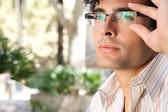 Young and attractive businessman looking up while holding his reading glasses with his hand. — Stock Photo