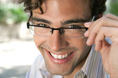 Attractive businessman wearing glasses and looking at the camera smiling — Stock Photo