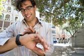 古典的な都市の外に立っている間彼の時計をチェックの若手実業家の肖像画. — ストック写真
