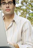 привлекательные бизнесмен в очках и с помощью портативного компьютера в парке. — Стоковое фото