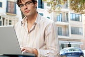 Attractive businessman wearing glasses and using a laptop computer in the city — Zdjęcie stockowe