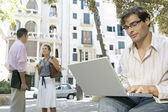 Portrait of a young businessman using a laptop computer in the city — Stock Photo