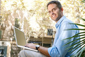 Senior businessman using a laptop computer while sitting on a bench in the city, turning to camera. — Stock Photo