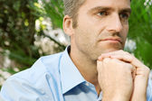 Portrait of a senior businessman sitting in a city park and holding his hands together under his chin — Stock Photo