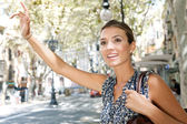 Attractive young businesswoman raising her arm to call a taxi in a busy city, outdoors. — Stockfoto