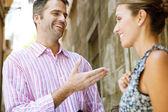 Zakenman en zakenvrouw hebben een geanimeerd gesprek in de buitenlucht — Stockfoto