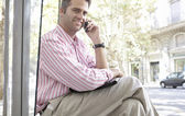 Businessman using a cell phone while waiting for the bus in the city, outdoors. — Stock Photo