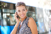 Attractive commuting businesswoman using her smart phone in the city — Stock Photo