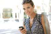 Young businesswoman using a smart phone while standing in a classic city street. — Stock Photo