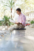 Businessman reading a newspaper while sitting down on a stone step in a classic city square — Stock Photo