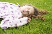 Yeşil çimlere bırakmasını ve palto giymiş bir kızın portresi. — Stok fotoğraf