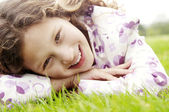 Porträtt av en ung flicka fastställande på grönt gräs i parken — Stockfoto