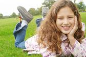 Ung flicka fastställande på grönt gräs i parken — Stockfoto