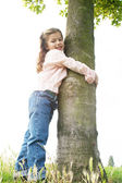 Young girl in the park hugging a tree on a hill, against the sky, and smiling to camera. — Stock Photo