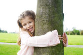 Smiling young girl hugging a tree in the park. — Stock Photo
