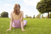 Back view of a young girl sitting down on green grass in the park — Stockfoto