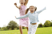 Two girls running towards the camera in the park. — Stock Photo