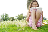 Young girl reading a book while sitting under a tree in the park. — Stock Photo