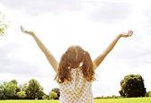 Meisje permanent in het park met haar armen gestrekt naar de hemel. — Stockfoto