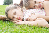 Two young sisters laying down on green grass in the park — Stock Photo