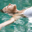 Attractive young woman floating on a spa's swimming pool — Stock Photo #21100137